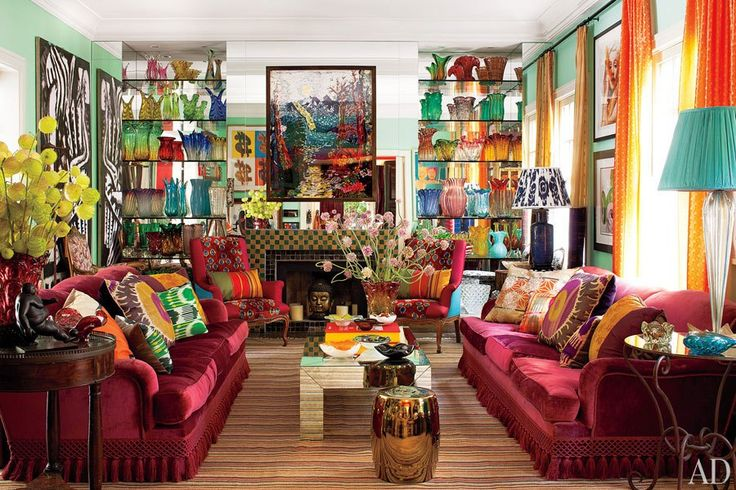 The living room is a cocktail of colors and cultures. Fringed sofas clad in a Rubelli velvet from Donghia are laden with vibrant pillows, and shelves showcase Murano-glass vessels; a Vik Muniz painting is displayed against the mirrored fireplace wall.