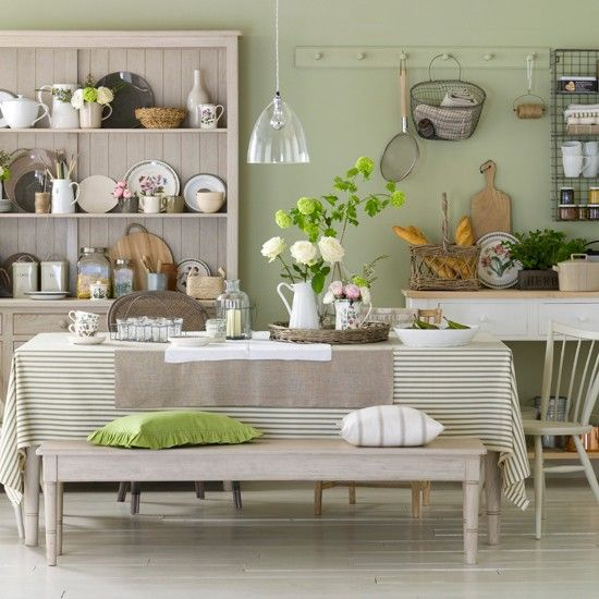 This pretty kitchen has an industrial-country feel with muted heritage colours, traditional ticking fabric and hints of fresh colour from botanical prints.