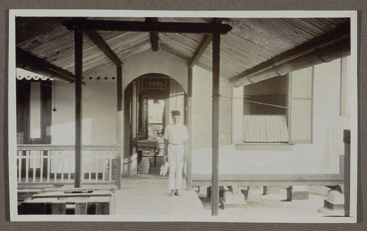 Anonymous | Indische man staand voor een deuropening in overdekte ruimte, Anonymous, 1920 - 1930 | Een Indische man staat voor een houten huis, mogelijk op een veranda. Hij is blootsvoets en draagt een hoofddeksel. Hij draagt zijn schoenen in zijn hand. Het huis staat los van de grond. Onderdeel van Familiealbum Nederlands-Indië.