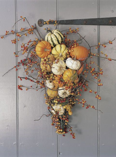 Bring on the decorative gourds! A bunch of mini pumpkins can outshine an average jack-o'-lantern any day. Throw them into a pretty cornucopia and you've got a one-of-a-kind door hanging to show off both on October 31 and throughout the autumn months. Click through for a tutorial and more DIY Halloween wreaths.