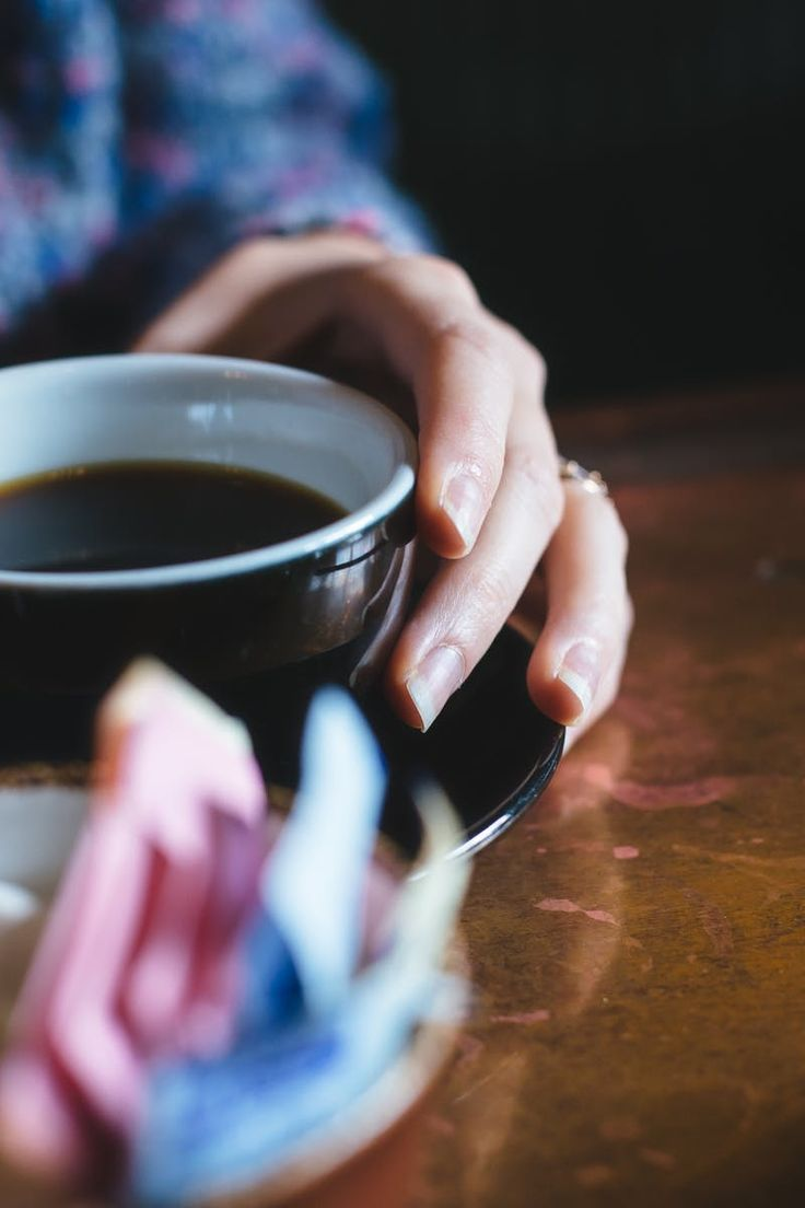 Woman Holding Black Ceramig Mug Filled With Black Coffee on Wooden Table