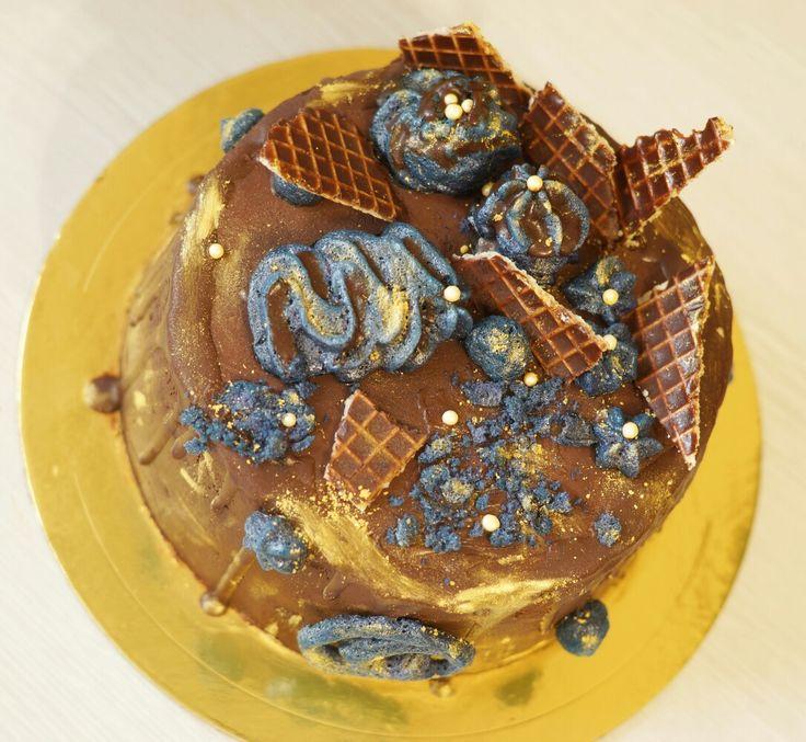 Мужской шоколадно шоколадный торт. Внутри шоколадный бисквит с шоколадным кремом. Сверху шоколадные подтеки и шоколадные вафли,  а так же меренги и сахарные бусины.