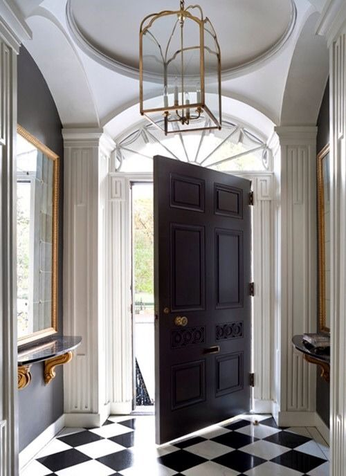Oversized door. Great entrance design. Black and white marble floor; deep grey walls with brass/gold accents. Beautiful!