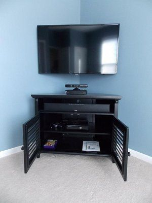 """42"""" TV mounted in a special corner mount with a Polk Audio soundbar and subwoofer that is hidden behind the cabinet."""