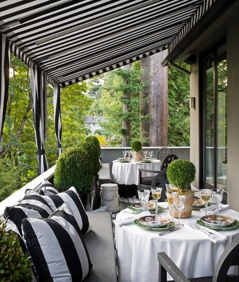 black and white striped awning over deck and striped outdoor pillows.