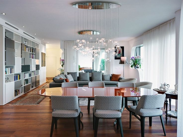 Apartments:Beautiful Open Plan Living Room With Dining Kitchen And Living Spaces White And Large Bookshelf Cascading Chandeliers Sofas Cushions Rugs White Curtains White Wall Laminate Floor Modern Interior Design of Luxury Apartment in Milan To Inspire You