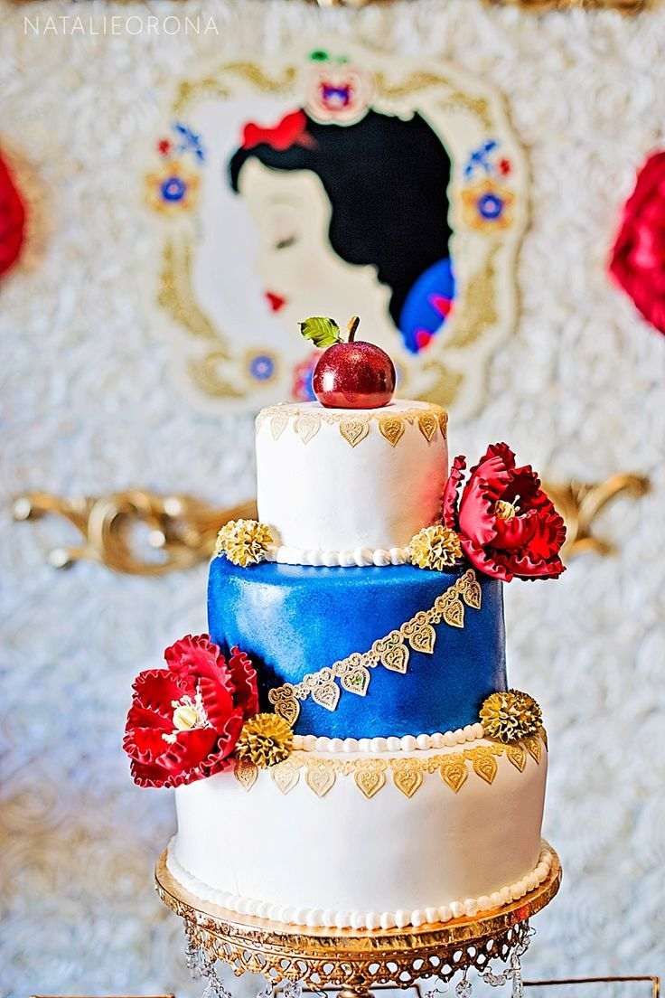 Elegant Snow White Inspired Cake by Heavenly Cakes N More. Royal Blue, Red & Gold colored Cake. Event by Storybook Bliss. Photography by Natalie Orona.