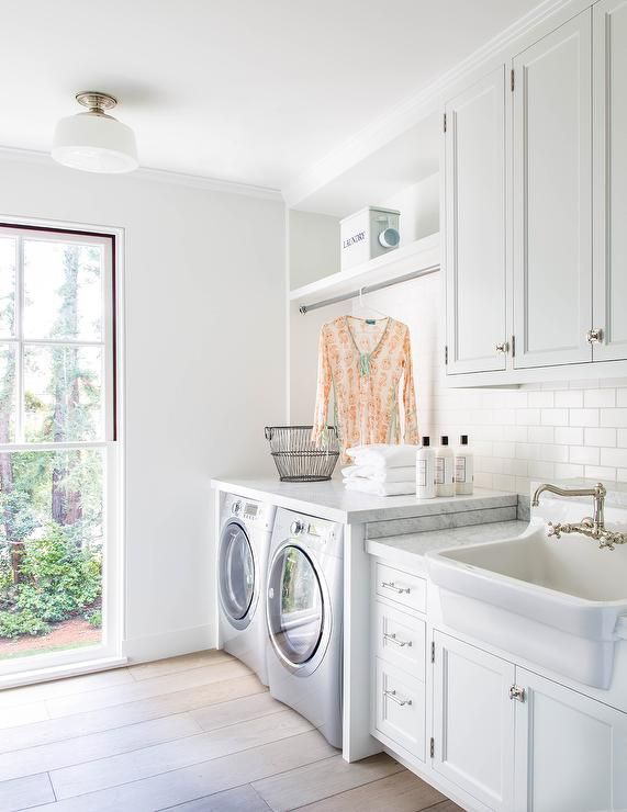 White laundry room features white cabinets adorned with vintage latch hardware paired with carrera marble countertops and a white subway tile backsplash.