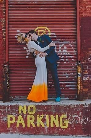 A modern groom kisses his bride, who wears a non-traditional dip-dyed orange wedding dress.