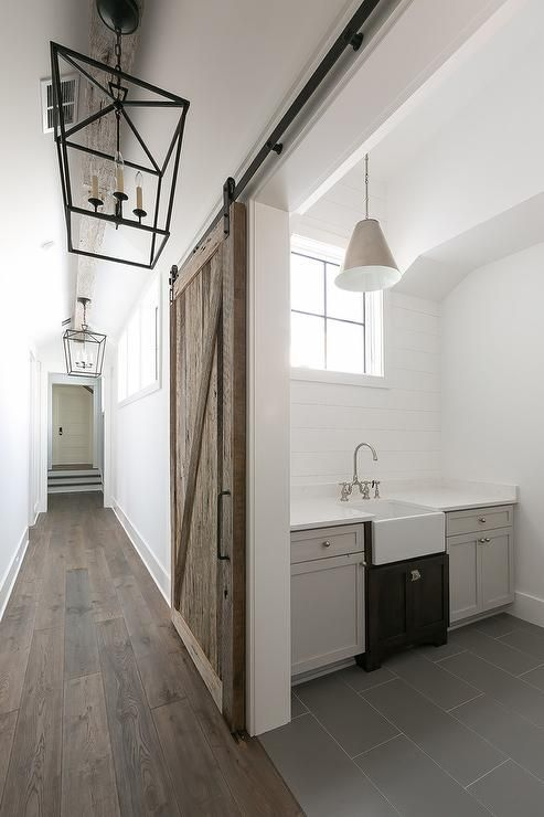 Cottage laundry room barn door on rails