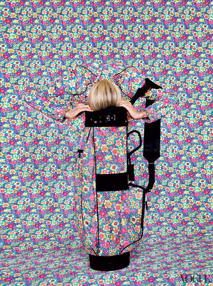 The kitschy sixties floral-wallpaper print is hardly par for the course but a standout on the green. Prada floral golf bag and jacket.