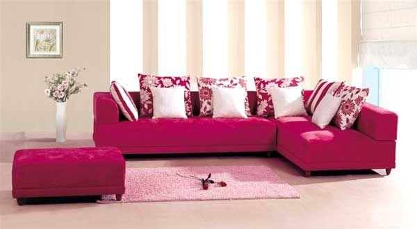 divano rosa con cuscini bianchi