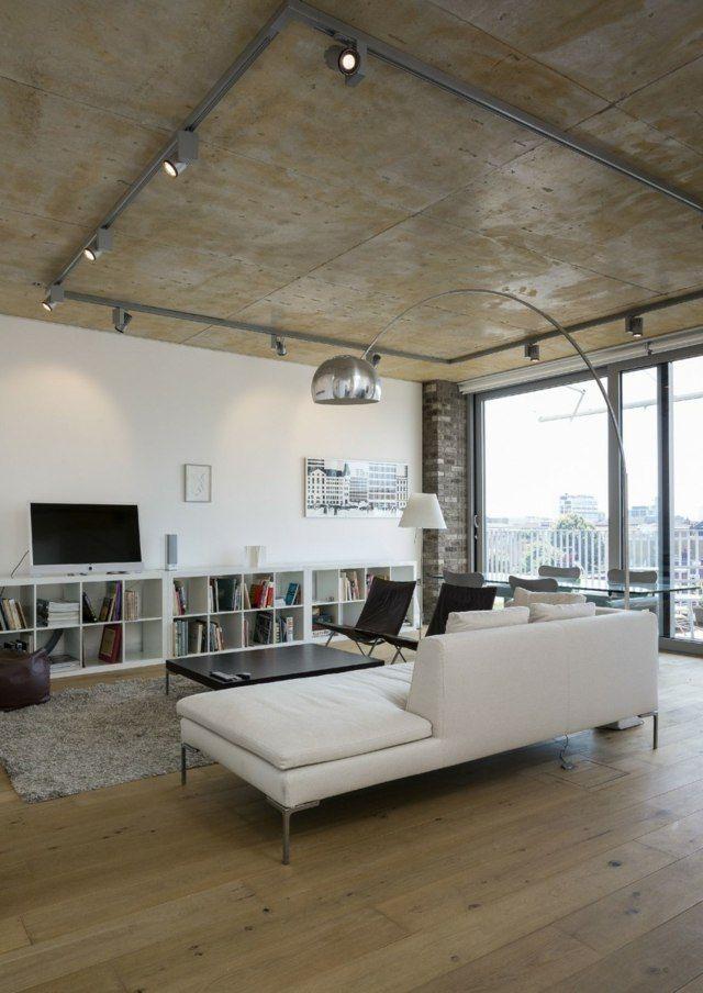 salon avec plafond en béton, spots sur rail et sol en bois