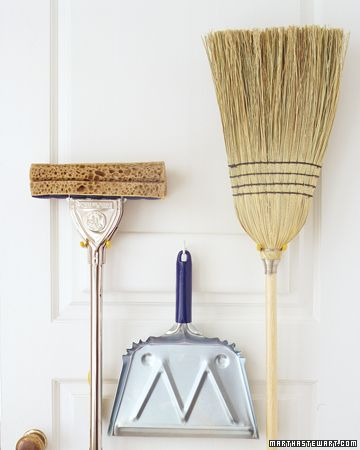"""Storing mops and brooms by standing them in a corner can cause broom straw to bend and mop heads to mildew. Instead use tool hooks (sold at hardware stores) to hang them with their """"business ends"""" up."""