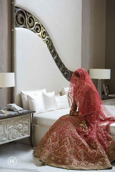 auburn red bridal lehenga from tarun tahiliani. All over intricate work bridal lehenga with veil, light veil on head, bride in dressing room, royal  regal, heavy,
