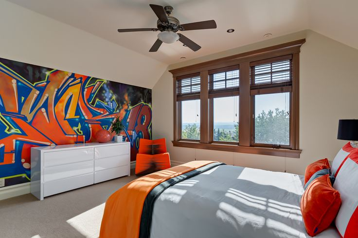 This home has a graffiti wall and an orange seat belt chair in one of the rooms. It is a fun bright and colourful. A sharp contrast to the transitional appearance of the rest of the home.