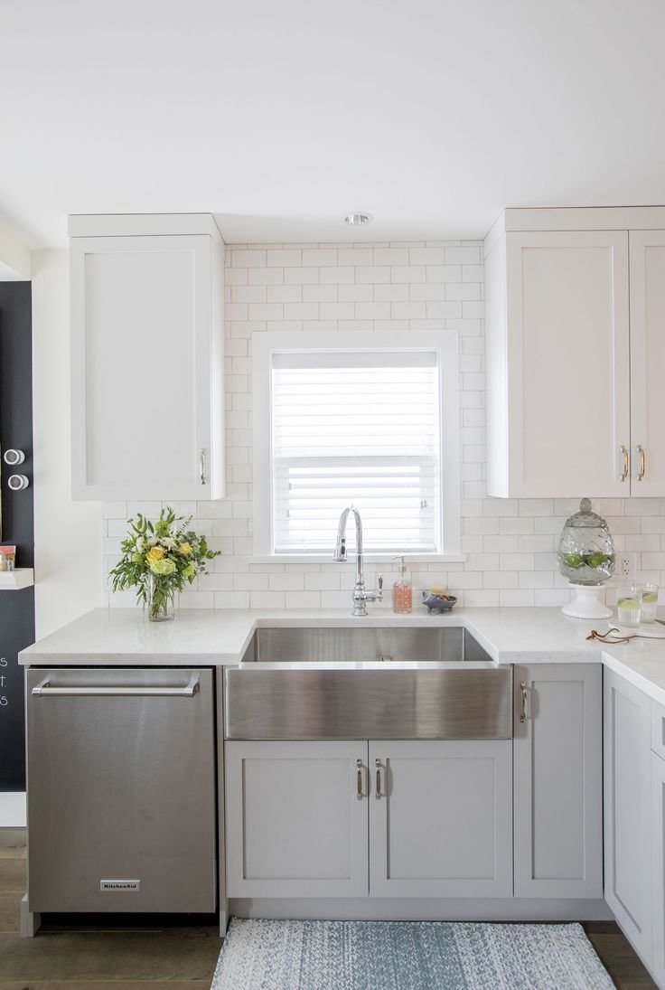 Brushed-steel apron sink makes a statement in this white kitchen