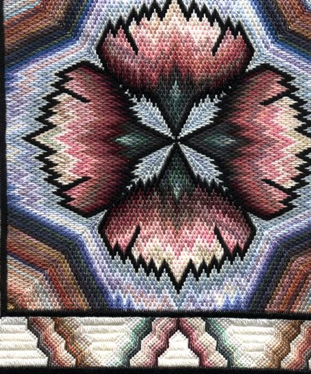 Partial scan of a pillow. It's a four-way bargello of a carnation motif, with a simple line repeat of the outer frame of the four carnations filling the center square.