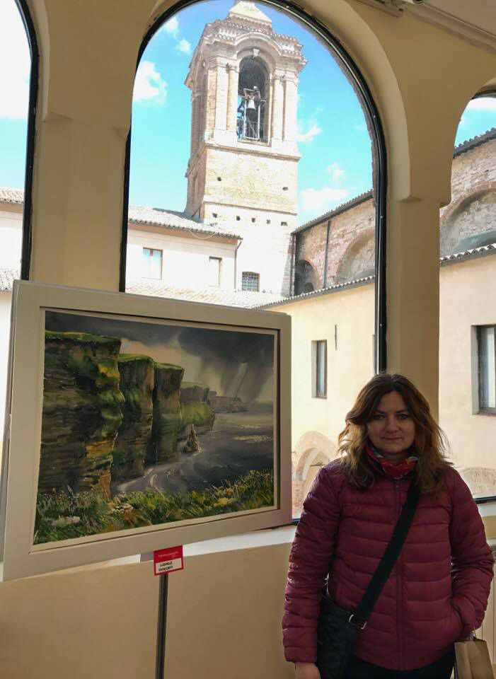Ludmila Korol with Cliffs of Moher painting in exhibition. IWS Fabriano, Italy