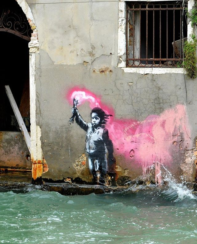 Banksy Reveals A New Mural In Venice Depicting A Migrant Child Wearing A Lifejacket Holding A Pink Flare This Comes On The Banksy Graffiti Banksy Banksy Art