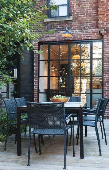 Black French doors, red brick and outside deck