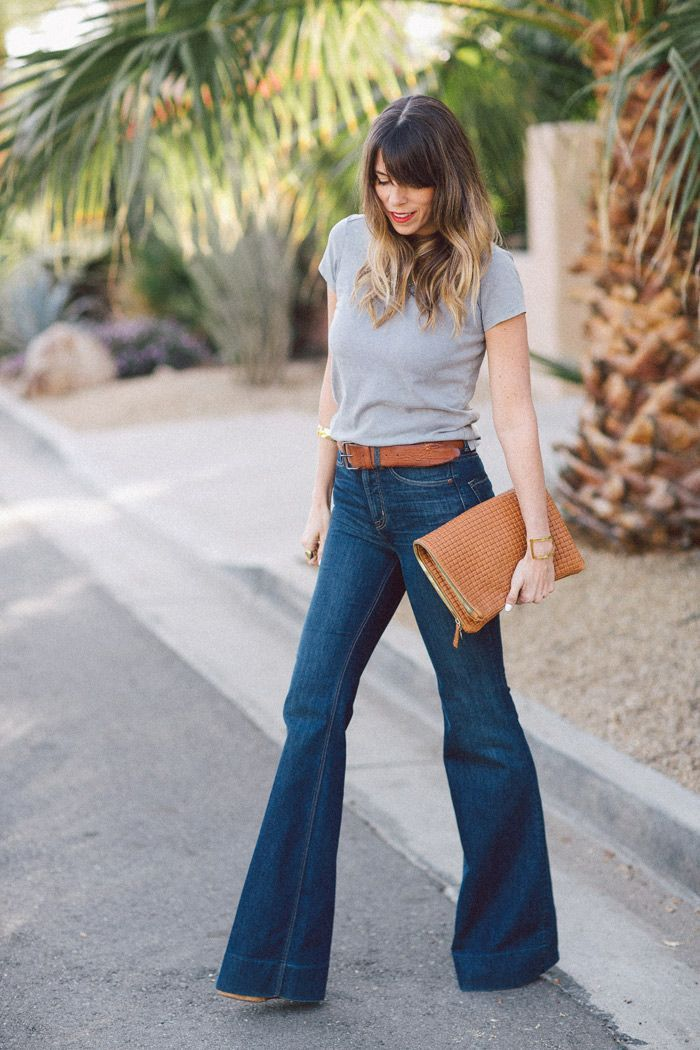 Shop this look on Lookastic: https://lookastic.com/women/looks/grey-crew-neck-t-shirt-navy-flare-jeans-tobacco-clutch-tobacco-belt/9280   — Grey Crew-neck T-shirt  — Tobacco Leather Belt  — Tobacco Leather Clutch  — Navy Flare Jeans