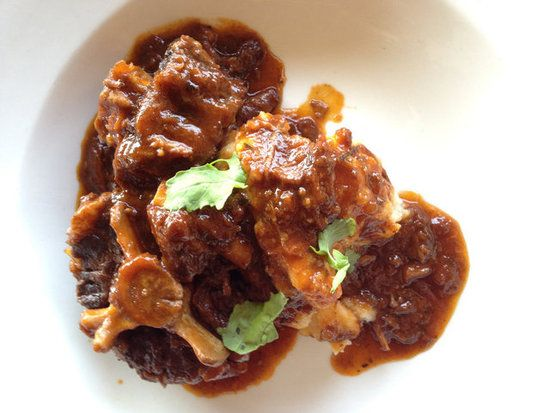 """Oxtail Potjiekos : Potjiekos (just say """"poikee-kos"""") is far simpler to enjoy than it is to pronounce. This dish — traditionally cooked over an open flame in a three-legged cast-iron pot called a potjie — often utilizes various cuts of meat, from lamb neck to oxtail. It's incredibly complex, thanks to the inclusion of Dutch-Malay spices, beer or wine, and a """"no-stir"""" rule."""