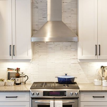 White cabinets with tile marble backsplash, stainless steel hood, and under-counter lighting.