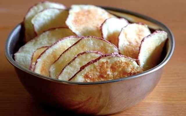 Самодельные картофельные чипсы. Самый тяжёлый момент в данном процессе – это максимально тонко нарезать картофель. Затем просто разложите картофельные дольки на тарелке и грейте в печи в течение 3 минут, периодически останавливая процесс, чтобы перемешать.