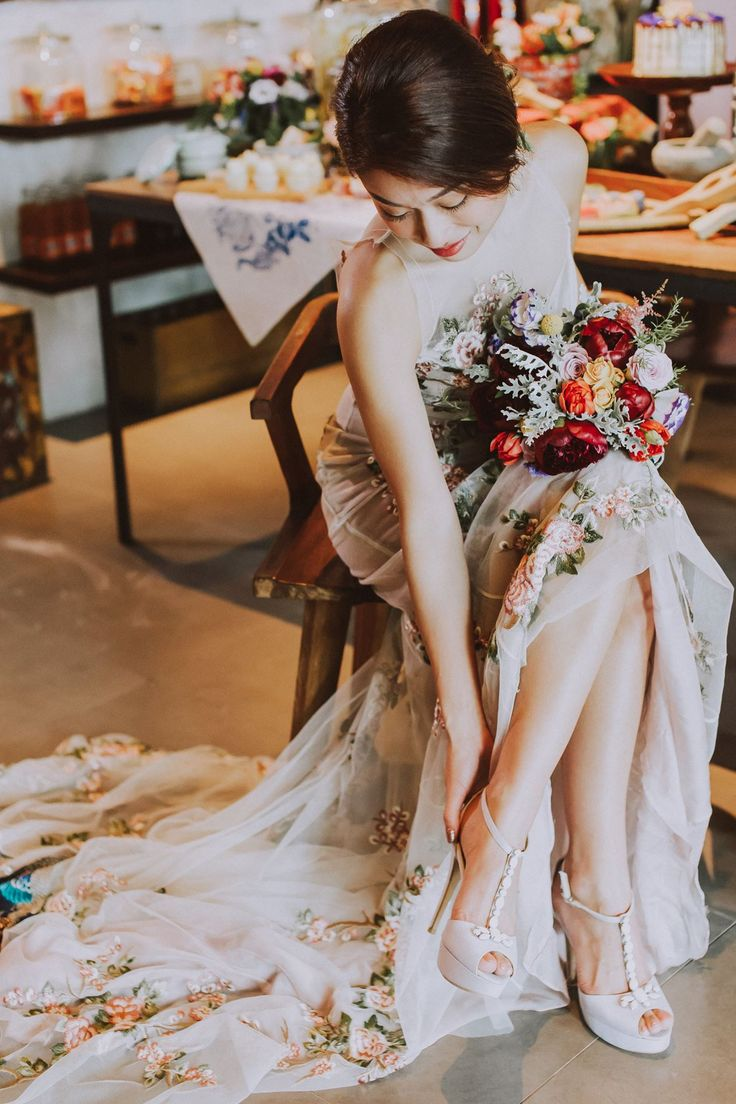 A gorgeous off-white peacock dress paired with tasteful stilettos and vibrant bouquet of white, orange, red and yellow // We hope you had a wonderful weekend, Wedding Scoopers! Here are some teaser photos from the Peranakan styled shoot we did in KL, Malaysia, that included this stunning wedding gown and the prettiest hand-painted macarons! We can't wait to share the whole set with you very soon!