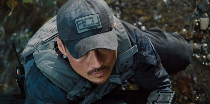 Jurassic World (2015) - Trailer Still Rather than entrusting the security of the park to a single sturdy Brit in shorts (RIP Muldoon), Jurassic World's owners have installed a small army on the island. They are the ACU, and this is Hamada (Brian Tee), looking up at something big and scary.