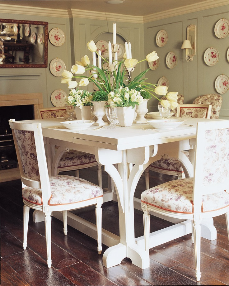 Love the pale green walls with the plates, fireplace, old wood floor, draw-leaf table, botanical print on the chairs
