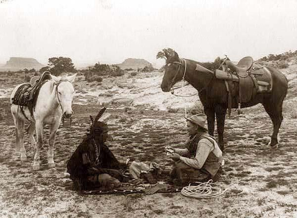 Cowboy and Indian seated on blanket playing cards photographed c. 1915 by William J. Carpenter.