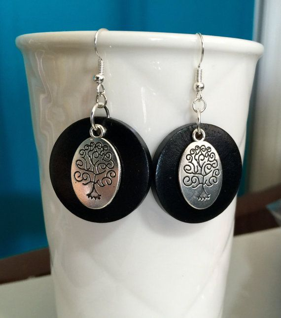 Lovely silver and black tree of life earrings. set on a light wooded disc. $9