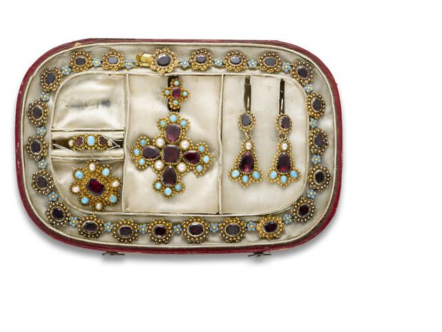 An antique garnet, enamel, seed pearl, turquoise and fourteen karat gold jewelry suite, late 1800's comprising: a necklace, brooch-pendant, brooch, ring and pair of earrings en suite; accompanied by a fitted box.