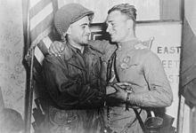 Battle of Berlin - 2nd Lt. William Robertson, US Army and Lt. Alexander Sylvashko, Red Army, shown in front of sign East Meets West symbolizing the historic meeting of the Soviet and American Armies, near Torgau, Germany.