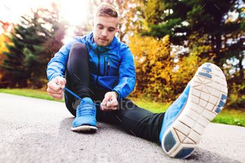 Handsome young runner sitting, tying shoelaces.