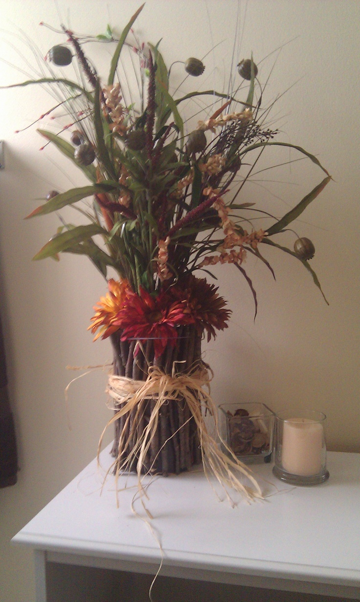 Oatmeal container with sticks hot glued on with a little raffia, potpouri inside and flowers to match the outdoor decor in our bathroom :)
