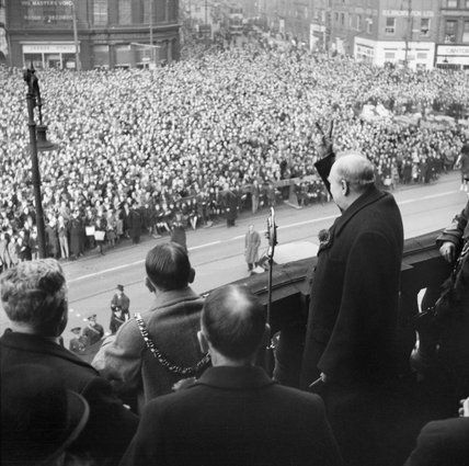 Horton (Capt) -- Winston Churchill gives his famous 'V for Victory' sign while addressing crowds from the balcony of City Hall in Sheffield, during a tour of the Midlands and North of England, November 1941.
