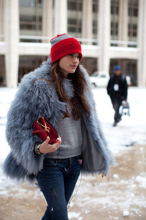 The bright red beanie makes another appearance, this time paired with puffy gray fur jacket over a sweatshirt and jeans.