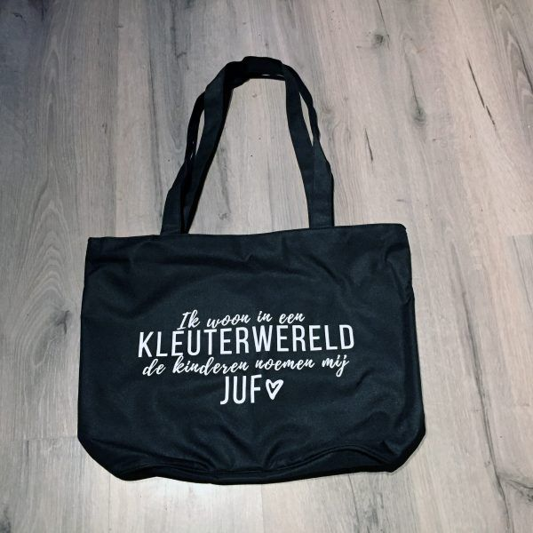 """Deze stevige kunststof tas is zwart met een witte opdruk.  """"Ik woon in een Kleuterwereld, de kinderen noemen mij juf""""  De tas heeft een rits en een klein binnenvakje (ook met rits) voor je kleine spullen. Zo hoef je niet je hele tas door te zoeken naar bijvoorbeeld je sleutels!"""