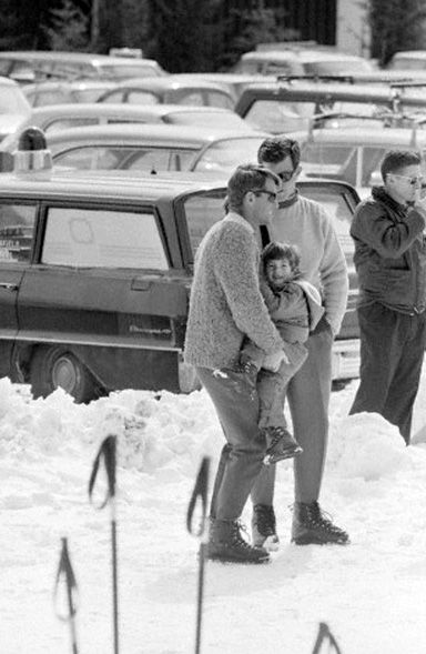 Robert F. Kennedy struggles to hold his nephew, John F. Kennedy, Jr., as he speaks with his brother Edward Kennedy. The entire Kennedy family was spending Easter in Stowe, Vermont (March 1964).