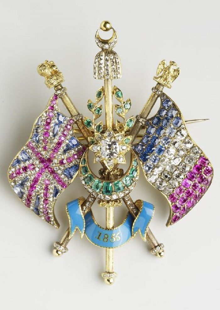 A Victorian 'Alliance Flag' brooch, by John Linnit, circa 1855. Silver, gold, rubies, sapphires, diamonds, emeralds, enamel. Presented to Queen Victoria from Prince Albert at Christmas, 1855. As a personal gift from Prince Albert, it was one of a select group of jewels specified by Queen Victoria in her will to be left to the Crown.