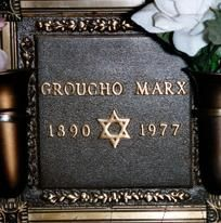 """Grave Marker- Groucho Marx, NYC, comedian (Marx Bros). He was cremated and the ashes were interred in the Eden Memorial Park Cemetery in Los Angeles.  In an interview, he jokingly suggested his epitaph read: """"Excuse me, I can't stand up."""" His mausoleum marker bears only his stage name, a Star of David, and the years of his birth and death.  (More go to: http://www.thefuneralsource.org/deathiversary/august/19.html)"""