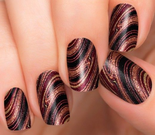 Marble nails are dazzling with a swirl of gold, rose gold, and black with a glitter finish.