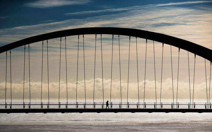 A person walks across the Humber Bay Arch Bridge during extreme cold temperatures in Toronto