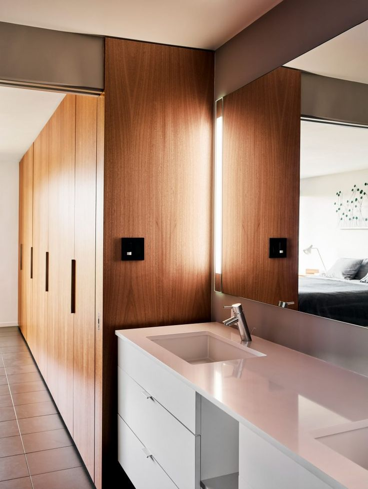 Love this mid-century inspired bathroom renovation. The white high gloss cabinetry works well with the tall wood storage cabinets
