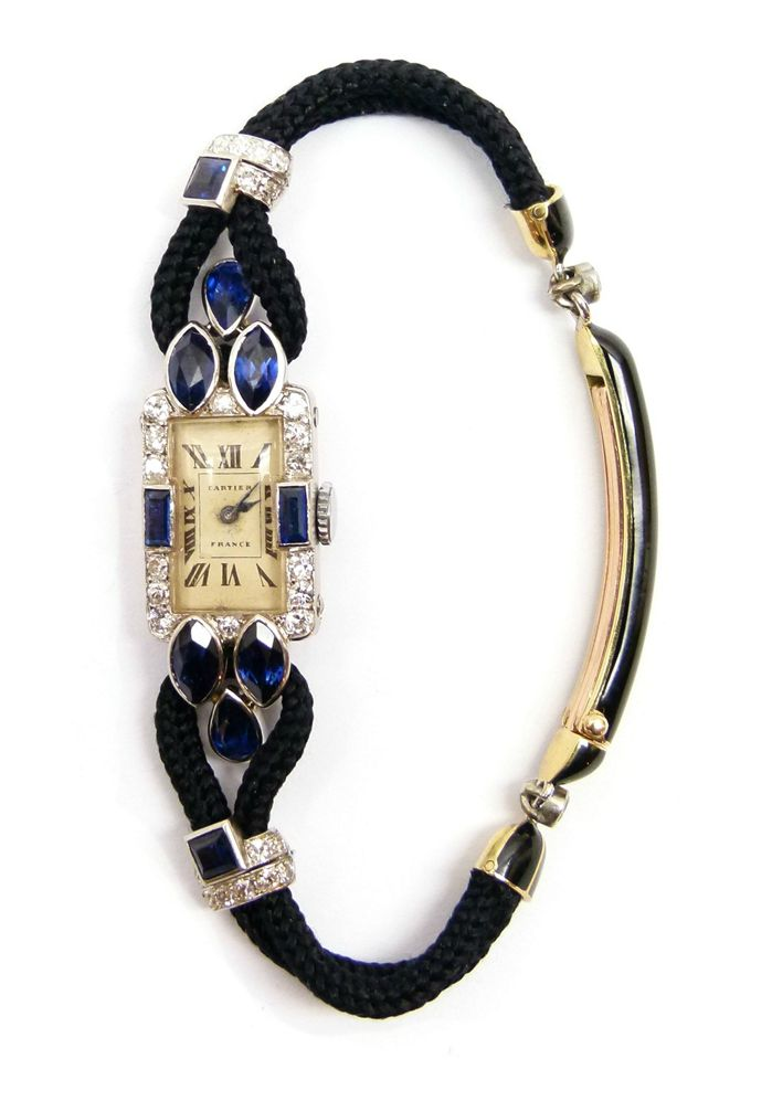 Art Deco sapphire and diamond lady's wristwatch by Cartier, Paris c.1925   , the cream rectangular dial with black Roman numerals, diamond set bezel with rectangular cut sapphires to either side, three sapphires of marquise and pear shape forming a triangle at the shoulders.