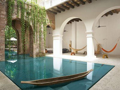 SO AWESOME! outdoor pool entering the home through an archway and becoming an indoor pool. Hammocks, secluded pool, beautiful vines...some of my favorite things put together!