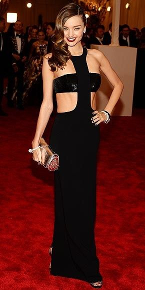 MIRANDA KERR - Met Gala 5-6-2013 Never one to miss the opportunity to remind us to go to the gym, Miranda shows off chiseled abs and enviably toned arms in a black Michael Kors halter gown with a coordinating bandeau bra, plus yet another spiked clutch that looks like it could do serious damage.